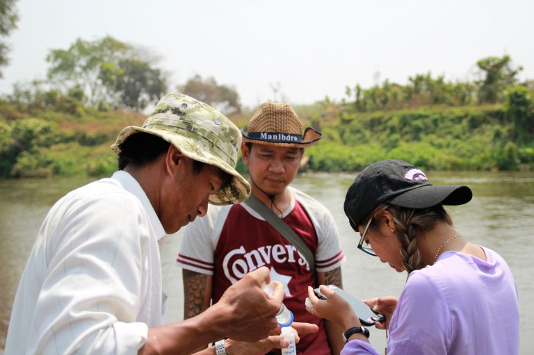 Three men in front of river taking water samples.