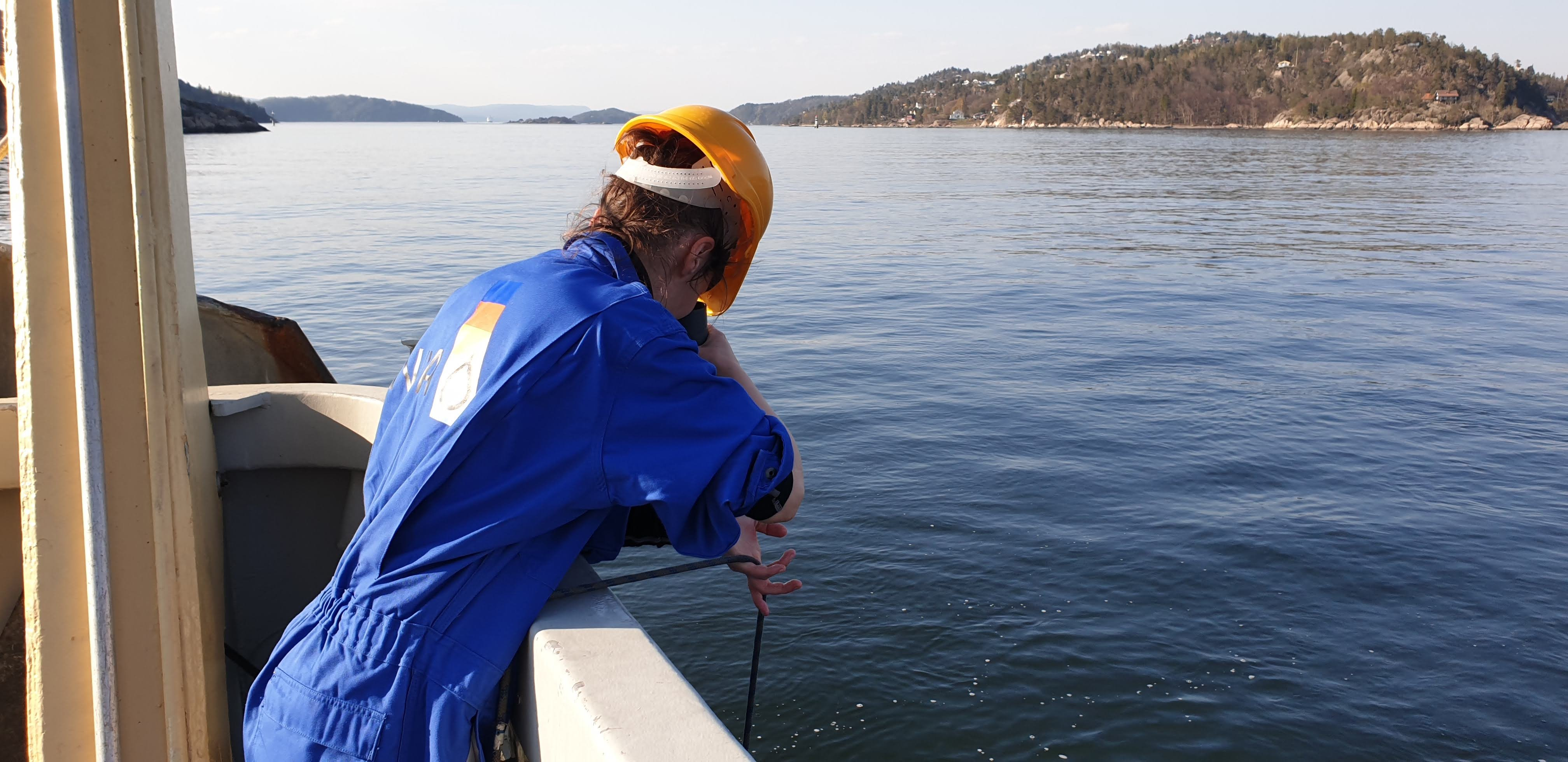 scientist on boat checking water quality in a fjord